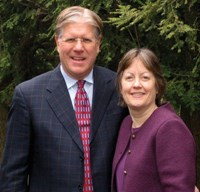 Kevin and Sharon Clark, a caucasian male and female; Kevin is in a grey, checked suit and Sharon is in a purple suit