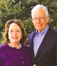 Ann and Charlie Marshall, a caucasian female and male; Ann in a purple suit and Charlie in a navy blue suit with glasses
