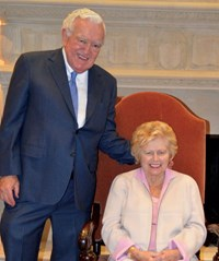 Dan and Margo Polett, a caucasian male and female; Dan is standing and in a navy blue suit, Margo is sitting and wearing a pink suit