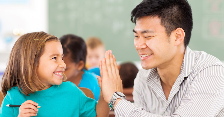 Asian American man in his late twenties  or early thirties gives his elementary school student a high five in the classroom.