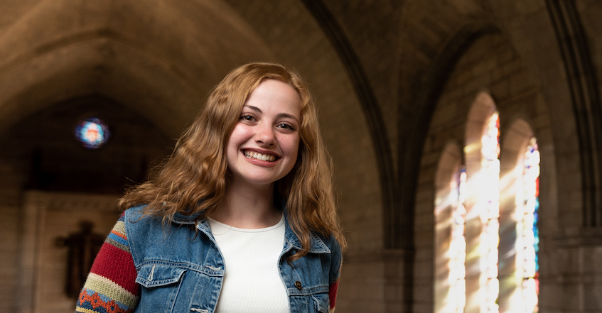 Undergraduate student smiles at camera. She has thick, wavy blonde hair and wears a denim vest over a white shirt. She stands ub front of a stained glass window inside a chapel.