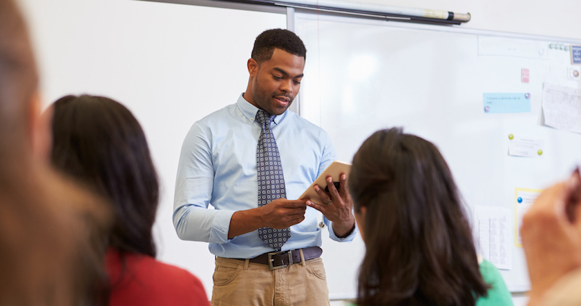 Young African American male stands in front of a classroom in business casual clothes. He wears a light blue button down shirt and tie and khaki pants. he is reading from a piece of paper and the back of his classmate's heads are visible.