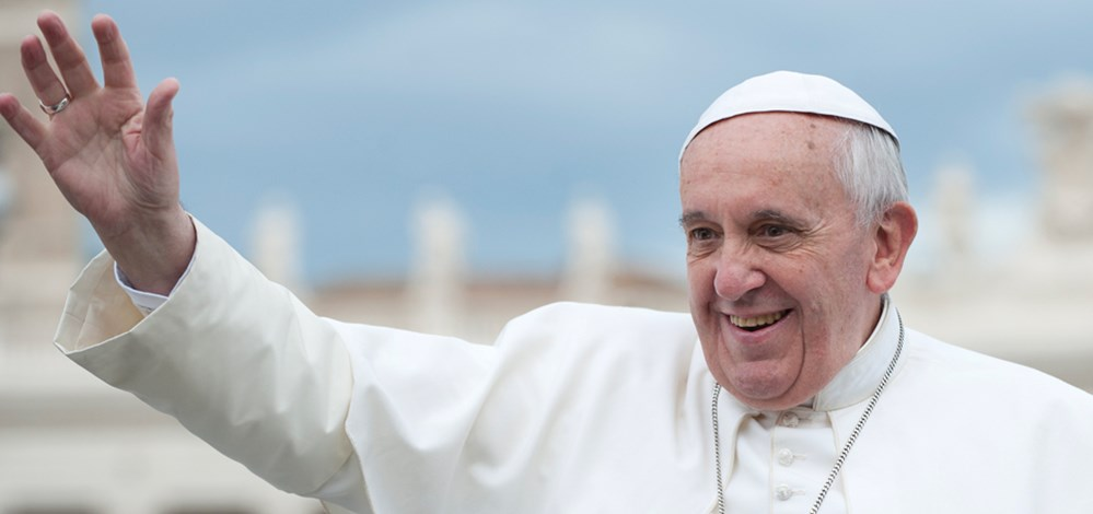 Pope Francis, a Latin American male, waving and smiling, in all white with blue sky in the background