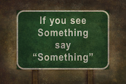 "green blackboard with chalk on it that says ""if you see something say something"""