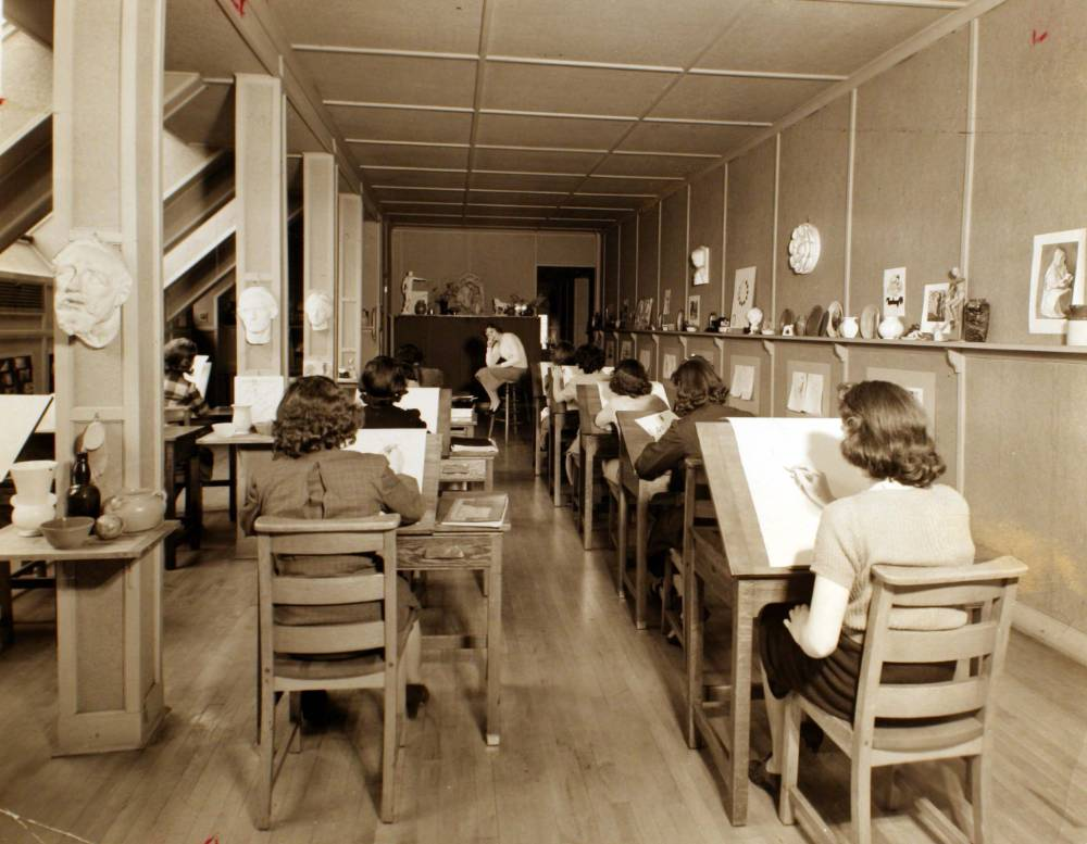Image of an art classroom in the 1930's. The back of all the female student's heads are visible as they draw a clothed model in a knee-length skirt leaning over on a stool with her elbow on her knee. The color of the photo is sepia-toned.