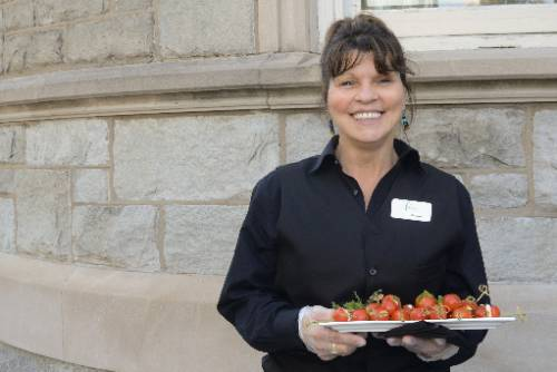 A smiling Latina cater waiter holds a silver tray in front of a grey brick building. She wears black.