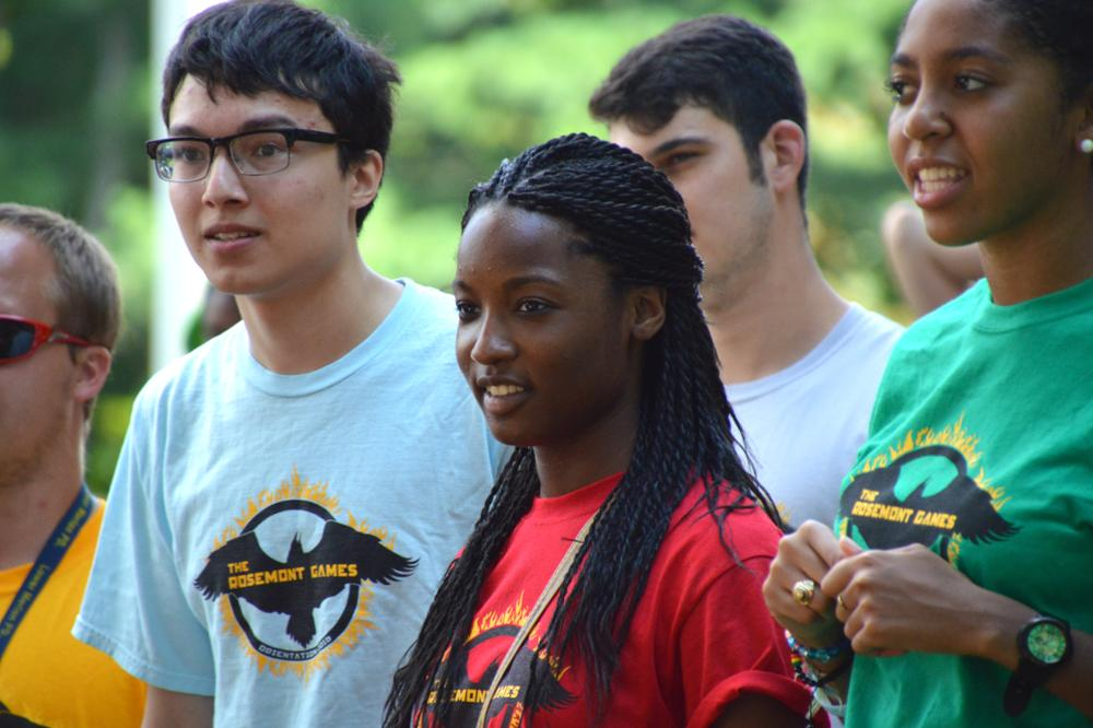Freshman students of various ethnic backgrounds and genders wear colorful tshirts and participate in an outdoor group activity for Student Orientation at Rosemont.