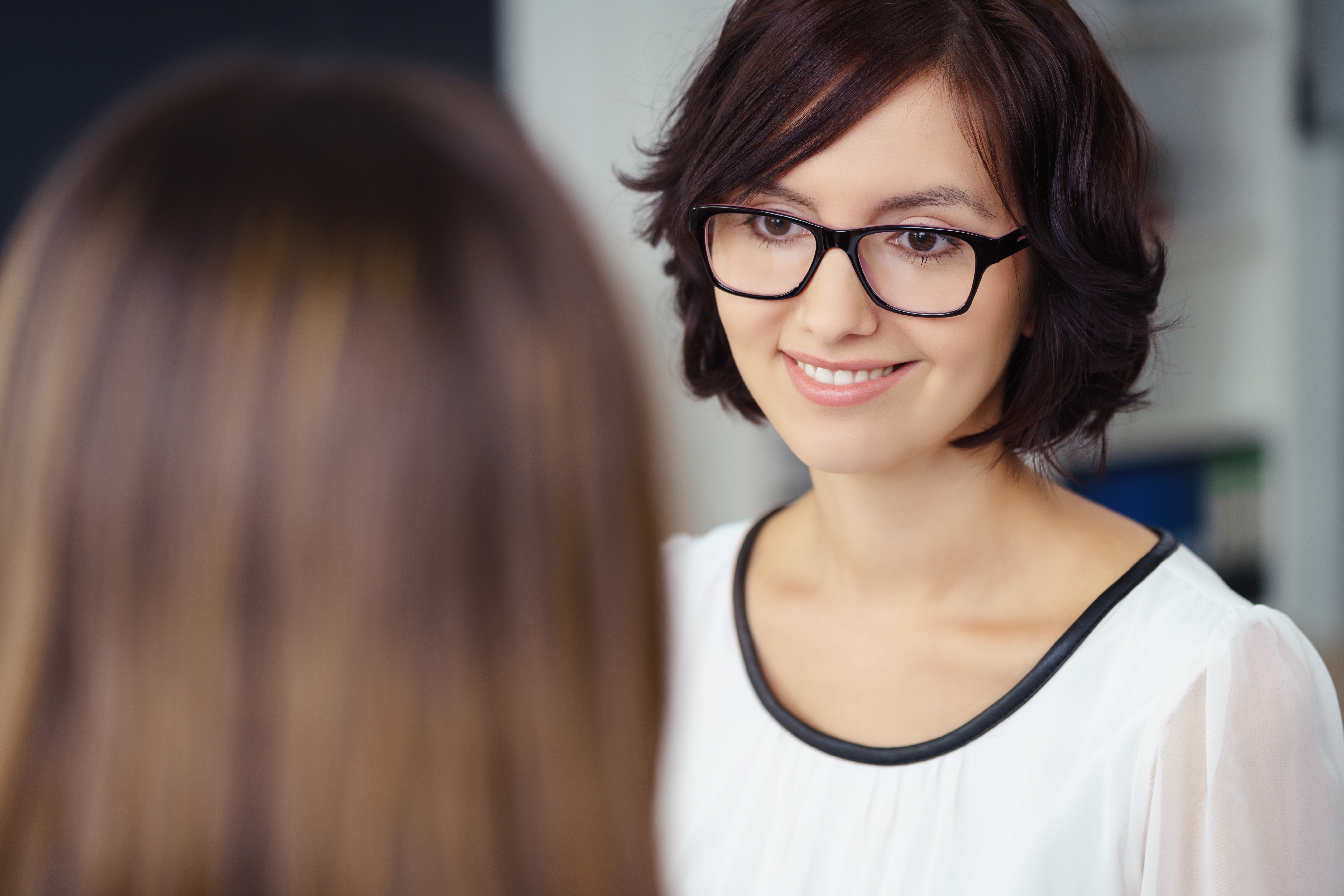 Image of young woman with short dark hair and glasses looking and smiling at her counseling client. The back of the client's head is visible, but you cannot see their face.