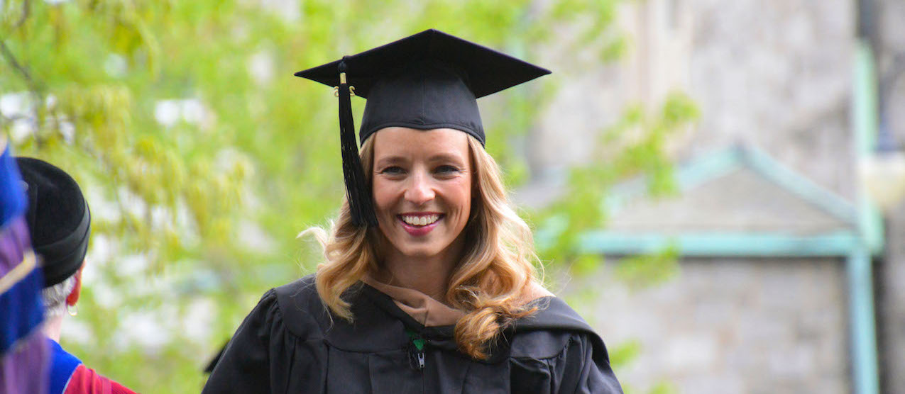 Image of attractive blonde female grad student in her commencement cap and gown.