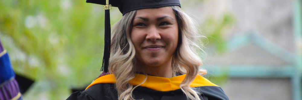 Adult student wears a cap and gown. She is of asian descent and has tan skin and bleached hair.