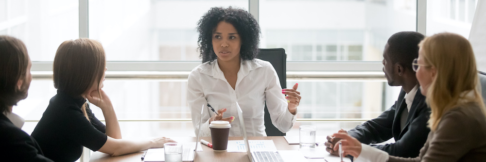 Confident young African-American business person leads a meeting. She wears a white button-down shirt and has full, curly hair.