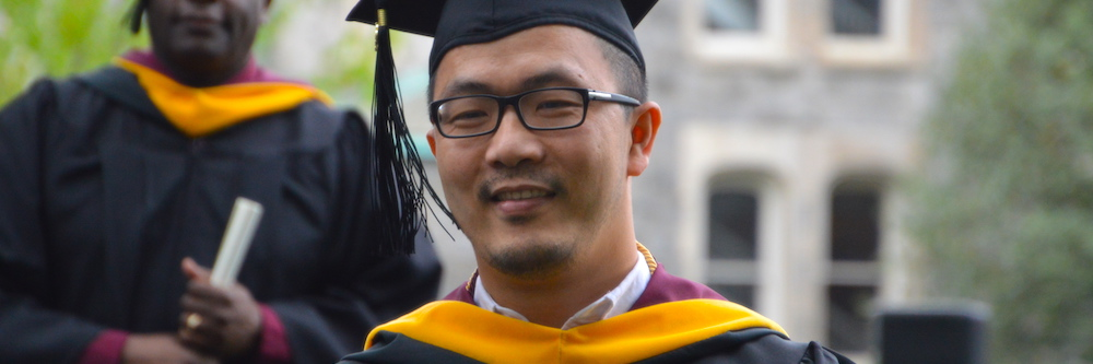 Thirty-ish Asian-American male grad student in his commencement cap and gown.