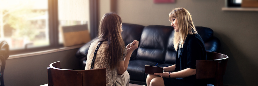 Two women are seen in a counseling office. One has straight blonde hair and wears black, professional-looking clothes. She appears to be the therapist. She is speaking with a client and the back of her head is visible. She has long  brown hair.