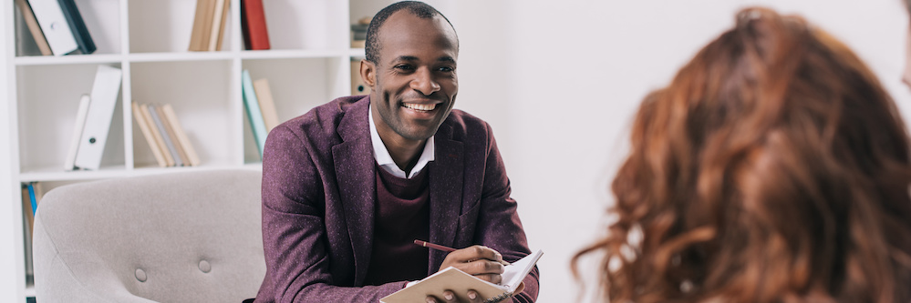 African American male therapist smiles at a patient across from his chair in a white, minimalist office. The back of the patient's head is visible, she is red-haired woman. A man's arm is slung around her shoulders. He has white skin.