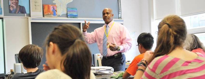 Adult African-American man with a shaved head, pink button-up shirt, light blue striped tye, and grey pants gestures in front of a classroom of adolescents.