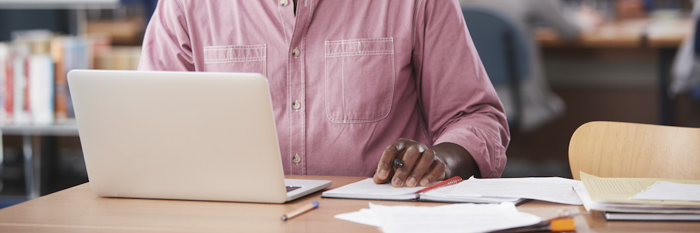 A pair of hands are pictured working on a laptop at a table. They belong to a an African-American male, and he wears a long-sleeved pink button down shirt.