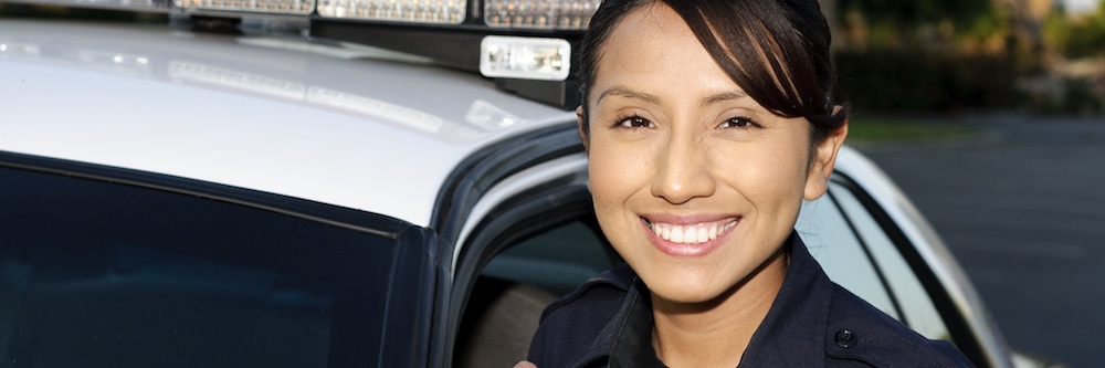Young woman of latin descent stands in front of a police car wearing her uniform. Her dark hair is pulled back and she has dark brown eyes.