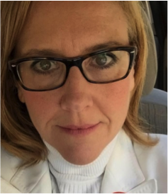 Picture of Professor and MFA Program Director Carla Spataro, a blonde woman with black-framed glasses and a white turtleneck shirt/jacket.