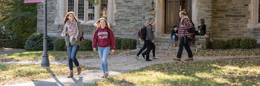 Students walk on a green college campus.