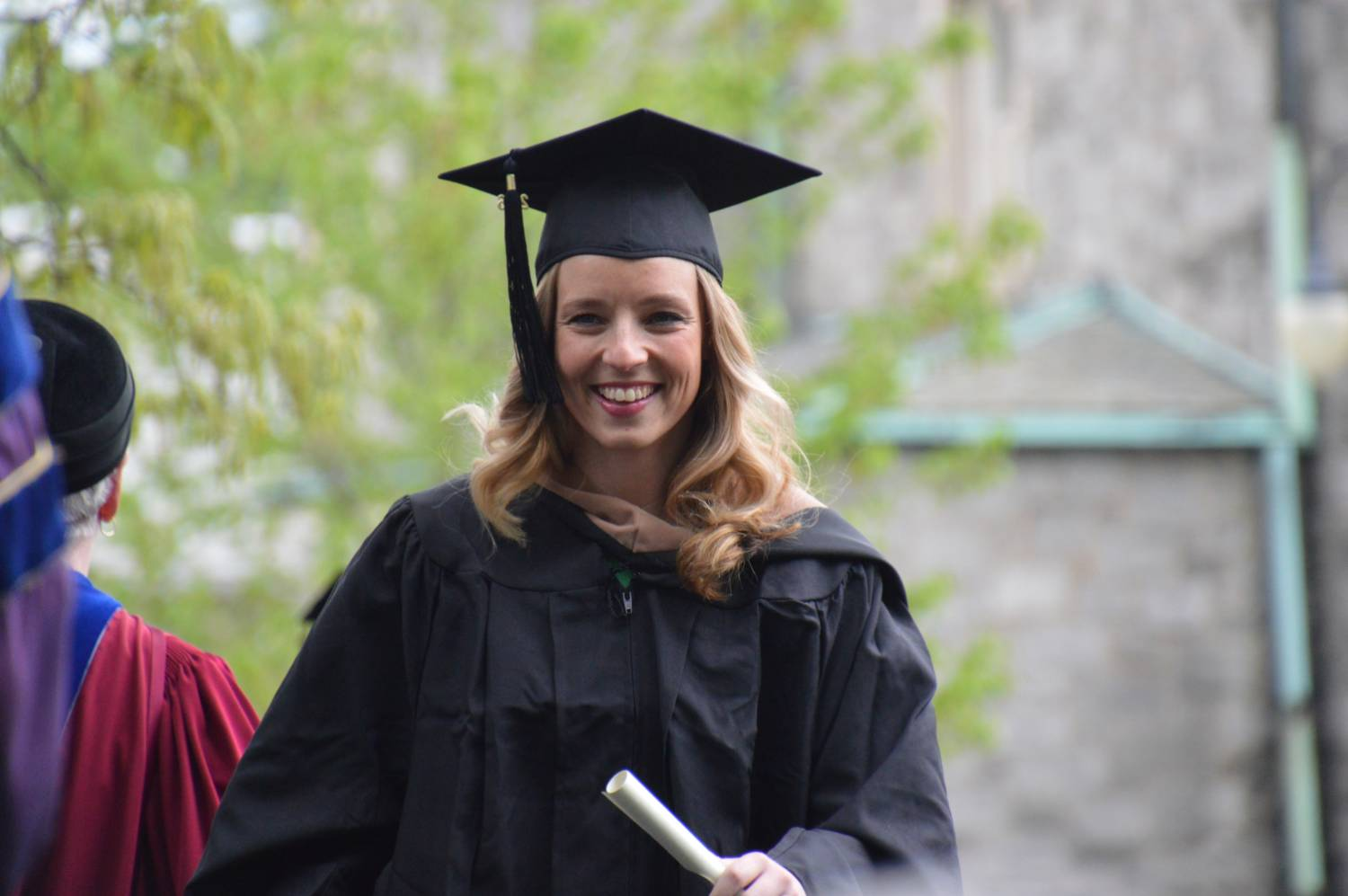 Woman in her thirties accepting a diploma in her cap and gown. She is caucasion with mid-length blonde hair.