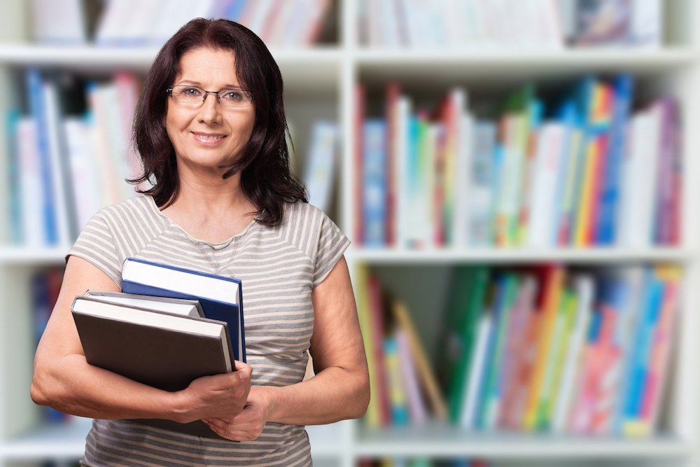 Photo of woman, possibly white or latina, in her fifties holding three hardcover books in a library. She is the the focal point of the image, and in the background there are shelves of books that are out of focus. She has shoulder-length dark brown hair, wears rectangular classes and has a light grey and white striped t-shirt on.