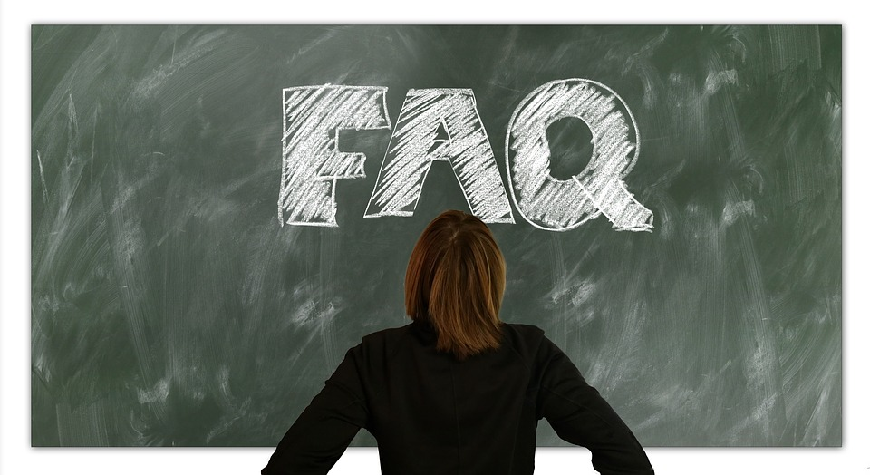 "A woman with brown hair faces a blackboard on which ""FAQ"" is written in white chalk."