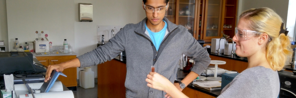 Two student scientist conduct an experiment in a lab.