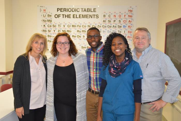 Science students stand with instructors in front of a periodic table.