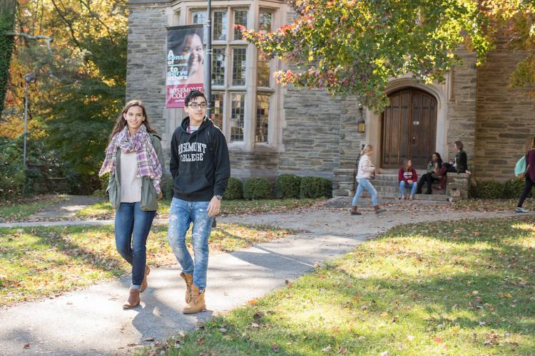Two undergraduate students are walking away from a building on a college campus. One is a slender girl with long wavy light brown hair and light skin. She wears blue jeans, boots, a jacket, and a pink and white checked light scarf. The other is a boy, slightly taller, with a dark blue Rosemont College sweatshirt, dark hair, tan skin, and boots that are untied at the top.