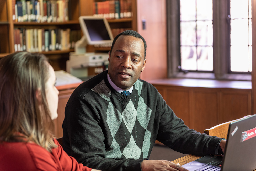 African American man in an argyle sweater sits with a student in the library and explains something.