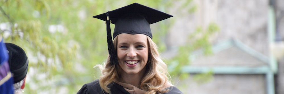 Blonde woman in a cap and gown smiling on a clear, sunny day.