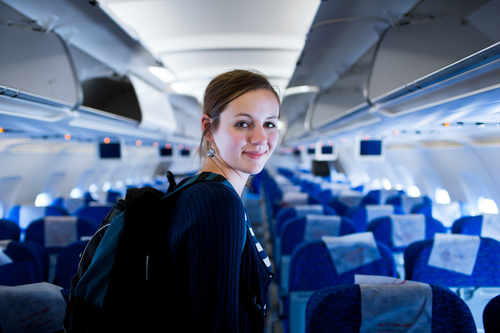 Image of young woman with dark hair on airplane.