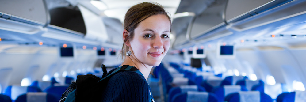 Young brunette white woman with olive skin turning back toward camera in the aisle of an airplane.