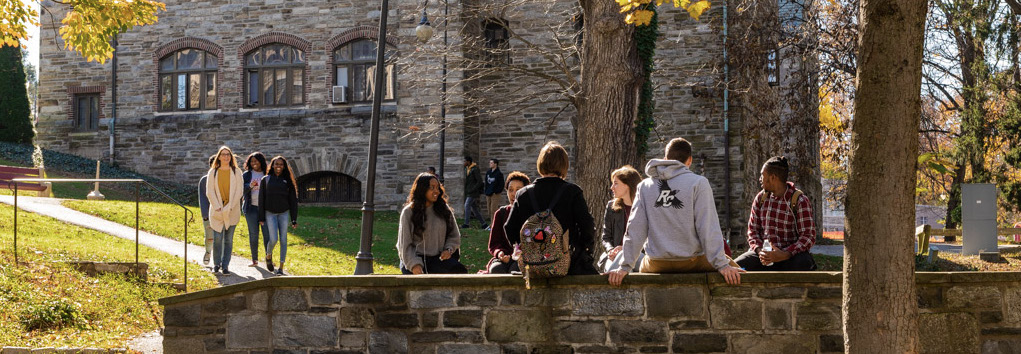 Students are pictured seated on a stone bridge of a very lush, green college campus. They vary in ethnicity and gender presentation.
