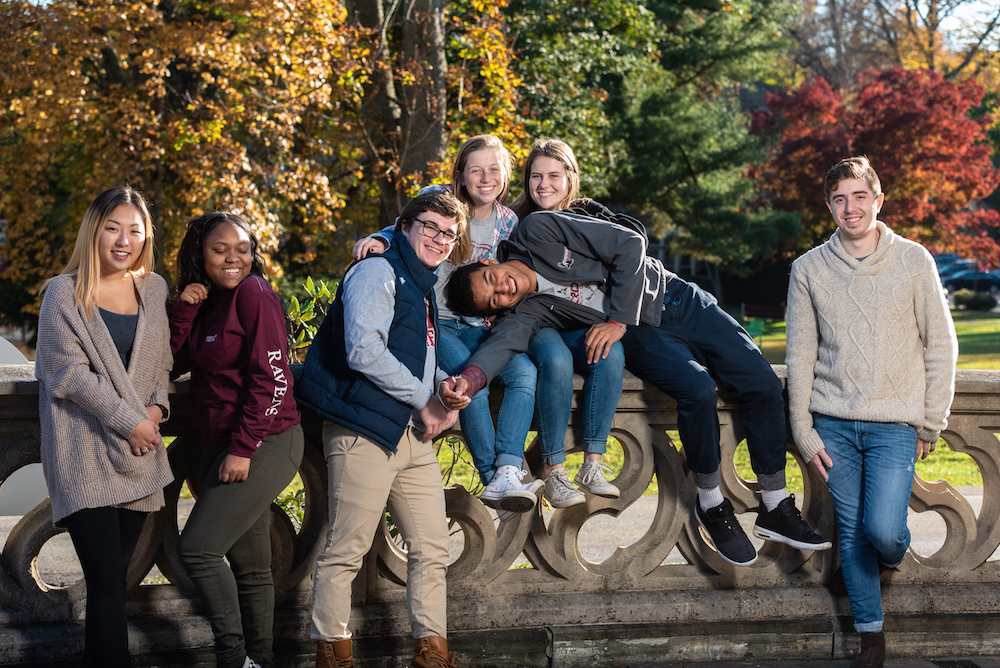 Group of multi-ethnic undergraduate students leaning against a low, grey stone wall.