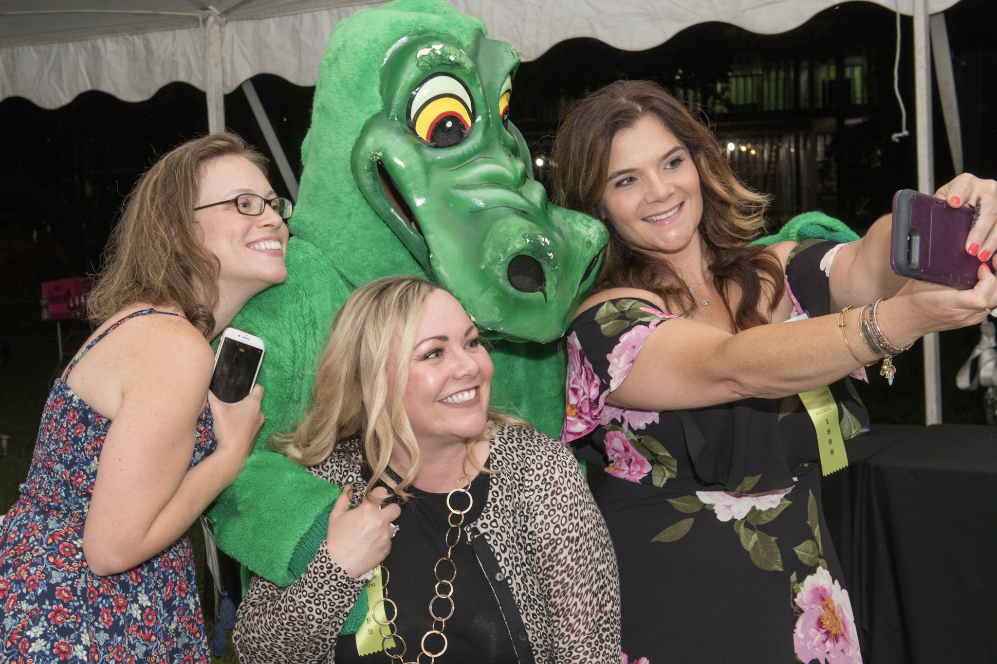 Image of three white women in their thirties at an outdoor event in summer dresses taking a photo with a big green college mascot that looks like a monster.