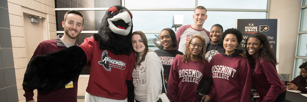 Renny the Raven is surrounded by a group of undergraduate students in their Rosemont apparel.