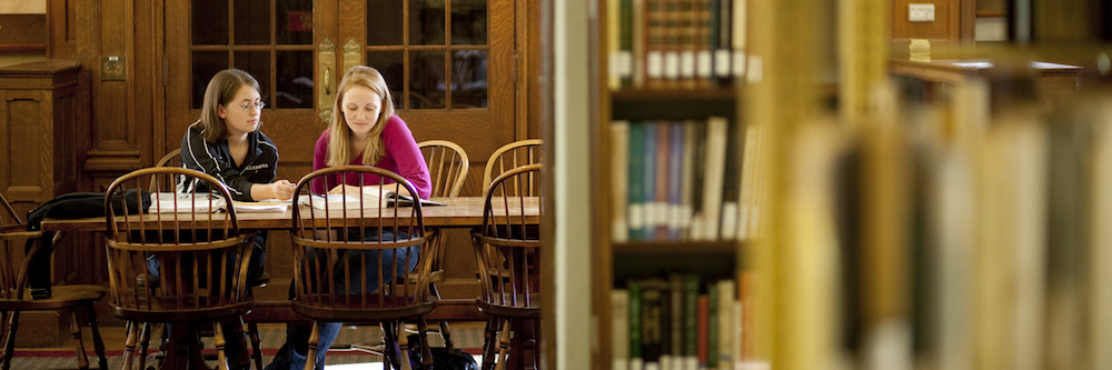 Two young women study in the library.