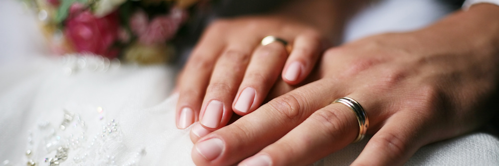 Image of a couple's hands wearing wedding rings.