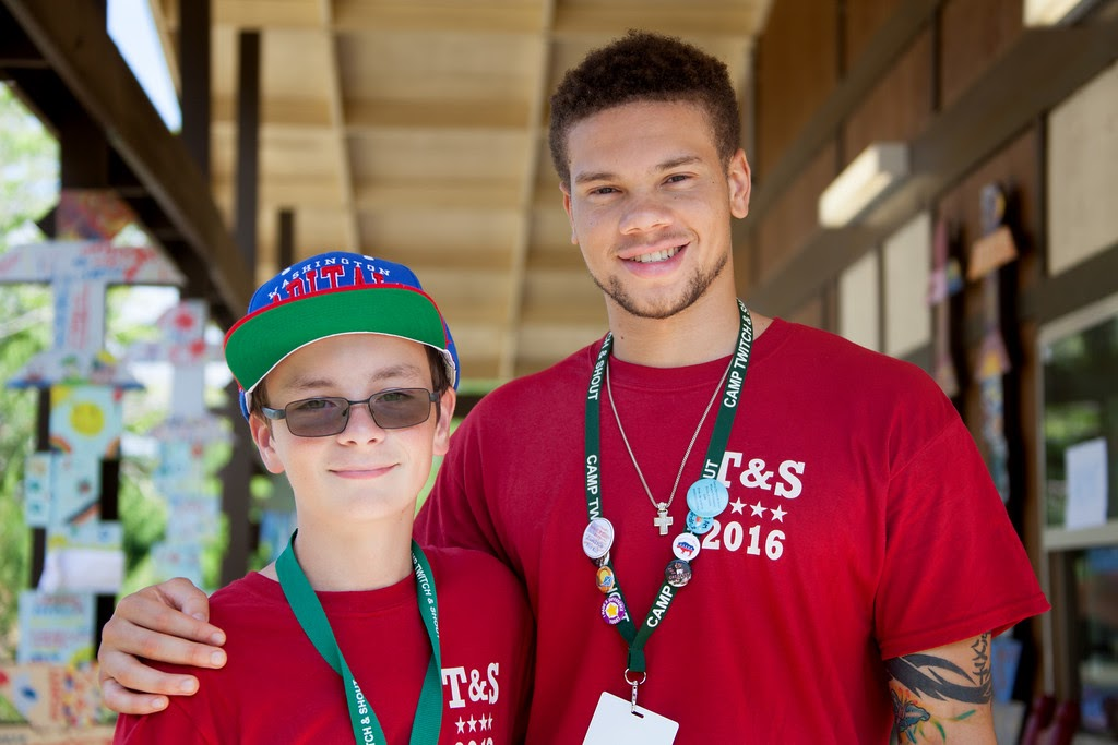 Photo of college-aged male with his arm around a younger boy who wears a red hat and glasses. Both wear red shirts and lanyards, and appear to be at a service event.