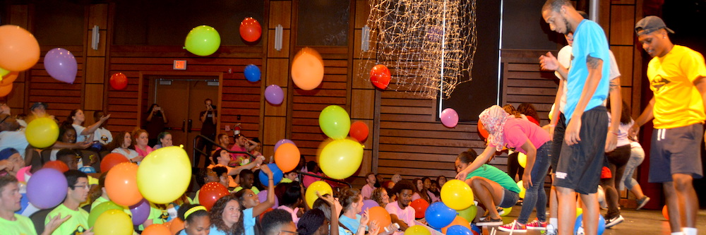 Orientation picture. Students are showered with colorful balloons in an auditorium. They all wear colorful t-shirts.